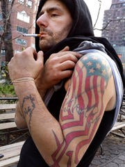 "Michael Cliff, a 32-year-old homeless man, shows off what he calls his ""American Dream"" tattoo while being interviewed in New York's Union Square Park. Cliff is one of several dozen homeless people that The Associated Press interviewed to get their impressions of government aid and shelter programs. ""I'm scared. I'm really scared I'm going to die out here when it's cold,"" Cliff said. ""But I won't go to a shelter, because you get raped there."""