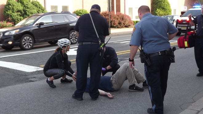 A Hawthorne man, seen lying down, is tended to by police, EMS and a passerby after he was struck by a pickup truck while crossing North Maple Avenue in downtown Ridgewood.