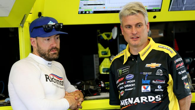 Driver Paul Menard and crew chief Matt Borland confer during practice for the 59th Daytona 500.