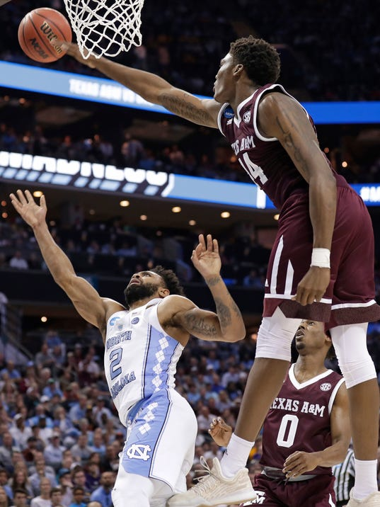 Texas A&M's Robert Williams (44) blocks a shot by North Carolina's Joel Berry II (2) during the second half of a second-round game in the NCAA men's college basketball tournament in Charlotte, N.C., Sunday, March 18, 2018. (AP Photo/Gerry Broome)