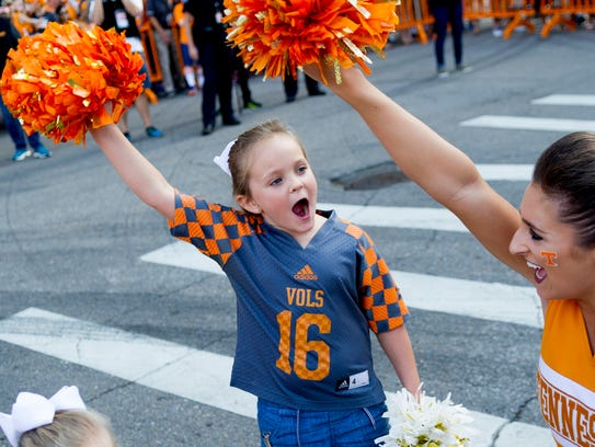 Kids cheer with a cheerleader during the Vol Walk during