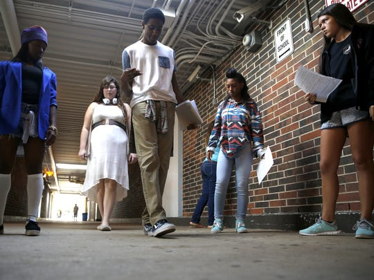 Christian Boyd, a junior at Godby High School, counts steps from two points in the high school's hallway as he and his STEM classmates work to determine scalars and vectors, calculating total displacement and distances for their Physics honors class.