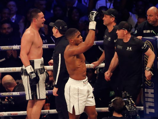 Britain's Anthony Joshua, centre, celebrates victory over New Zealand's Joseph Parker, left, after their WBA, IBF, WBO and IBO Heavyweight Championship title bout in Cardiff, Wales, late Saturday, March 31, 2018. (AP Photo/Frank Augstein)