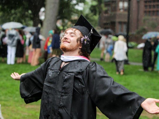 A graduate welcomes the rain during Vassar College's 2015 Commencement Ceremony.