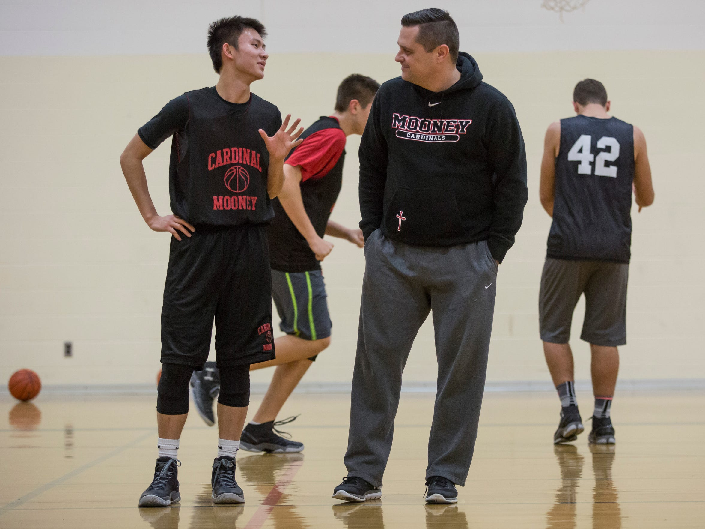 Senior Chris Xuan, 19, chats with coach Mike McAndrews during basketball practice Wednesday, Jan. 27, 2016 at Cardinal Mooney High School in Marine City. Xuan is an exchange student from Shenzhen, China.
