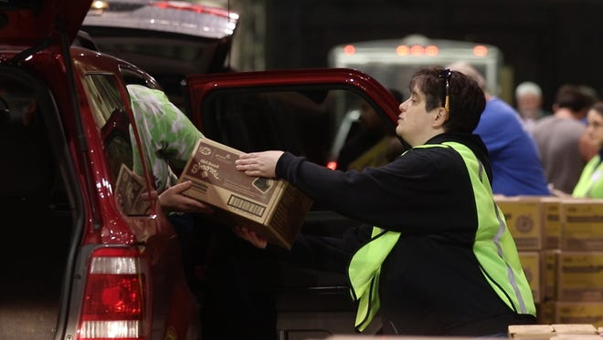 Lani Sherrill, manager of volunteer training and development with the Girl Scouts of Western New York, helps with loading vehicles with cookies.  A little over 400 troops in the Rochester area sold 42, 000 cases of Girl Scout cookies.  The average box sold per girl was 155 packages.