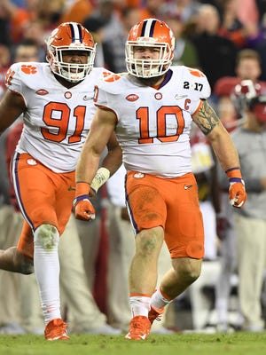 Clemson linebacker Ben Boulware (10) celebrates after bringing down Alabama running back Damien Harris (34) for a loss during the 4th quarter of the National Championship at Raymond James Stadium in Tampa on Monday. Also pictured is Clemson defensive lineman Austin Bryant (91).