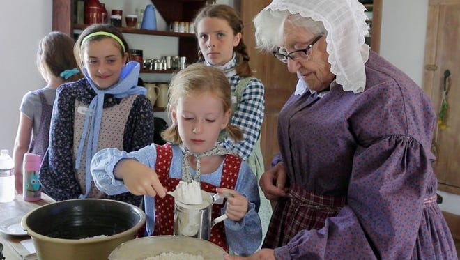 Children learn pioneer cooking during Pioneer Day Camp at the Wade House in Greenbush.