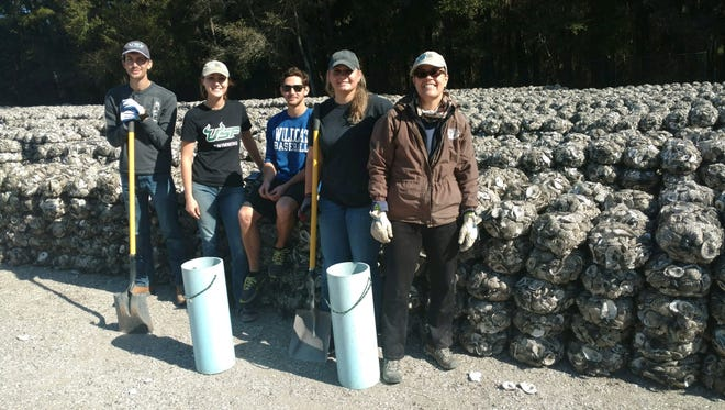 From left, Josh Richards, Hannah Edwards, Michael Hopko, Brooke Kerns and Shelley Mangram participate in the Jan. 19, 2018, bagging event with the Escambia County Living Shorelines Project at Navy Point.