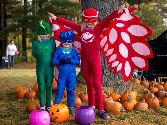 Siblings Auria Hollenbeck, 4, Lorly, 3, and Quira, 6, post in their PJ Masks costumes during a trunk-or-treat Saturday, Oct. 22, 2016 at St. Clair Township Park.