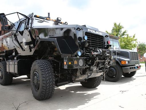 Bigger is better? Lawrence Police Sgt. Tom Reuss is dwarfed by the department's new military MRAP vehicle (left). At right is the city's former SWAT vehicle, a Brinks armored truck.