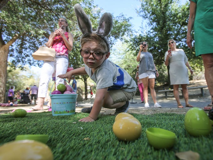 Preston Floss, 2, gathers Easter eggs at Gecko Gulch