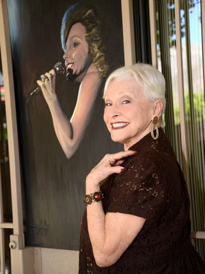 """Judy Bell, a former Palm Springs Follies performer, poses beside an early portrait of her at her Palm Springs condo. She is a headliner at the """"Thanks for the Memories"""" tribute show."""