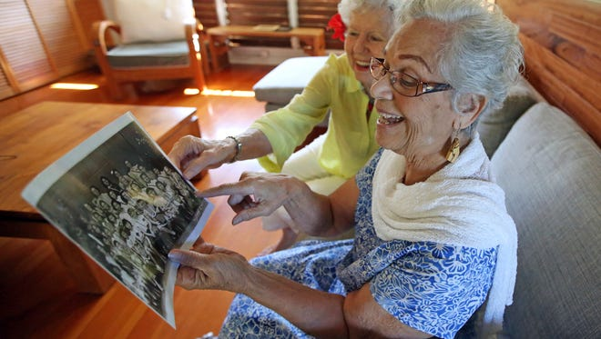 In this Friday, Nov. 18, 2016 photo, Joan Martin Rodby, left, and Emma Veary look at their fifth-grade class photo during a reunion in Makawao, Hawaii. Rodby remembered the carefree walks to school, and her family building an air raid shelter in their yard. Veary reminisced about her days singing, and when her family covered the windows at night so Japanese pilots couldn't use the light of homes to guide them. (AP Photo/Rick Bowmer)