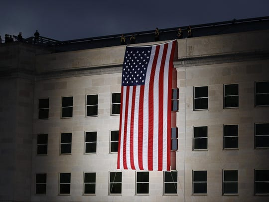 An American flag is unfurled at sunrise at the Pentagon in Washington on the 18th anniversary of the September 11th attacks, Wednesday, Sept. 11, 2019. (AP Photo/Patrick Semansky)