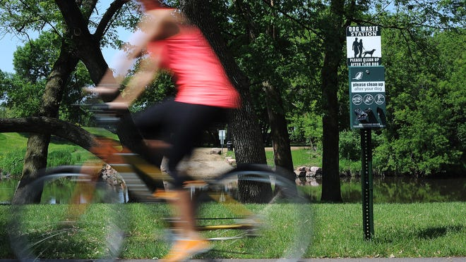 A bicyclist rides past a dog waste station on the bike trail in Rotary Park on Wednesday, May 27, 2015, in Sioux Falls. The city of Sioux Falls is installing 24 dog waste stations along the bike trail and in public parks. RIGHT: Kelby Mieras, park operations manager with the city of Sioux Falls, speaks during a press conference on Wednesday, May 27, 2015, in Sioux Falls.