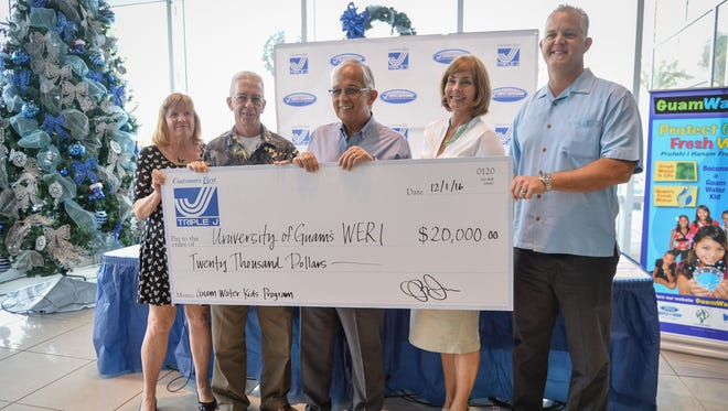 Triple J Enterprises donates $20,000 to the University of Guam Water and Environmental Research Institute for its Guam Water Kids outreach program, at Triple J Motors on Dec. 1, 2016. From right are Jay Jones, senior vice president of Triple J Enterprises; Cathleen Moore-Linn of the UOG Research Corporation; Robert Underwood, UOG president; John Jenson, WERI director at UOG; and Ann Card, grant administrator for Water Kids.