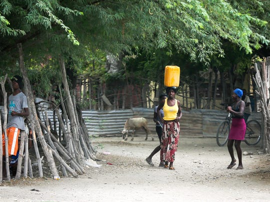 A woman carries water in Chambrum, Haiti.
