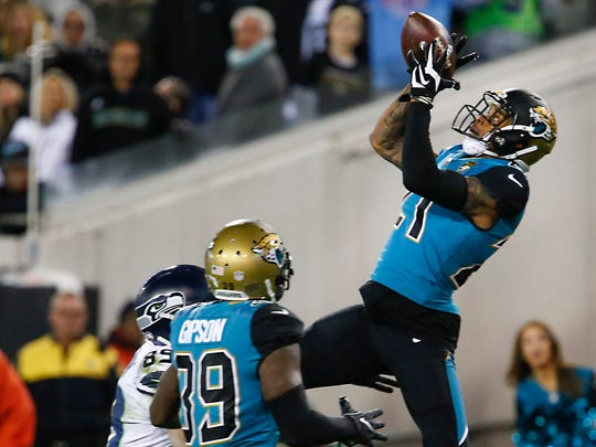 Jacksonville Jaguars cornerback A.J. Bouye (21) intercepts a pass intended for Seattle Seahawks wide receiver Doug Baldwin (89) as Jaguars free safety Tashaun Gipson (39) assists during the second half at EverBank Field.