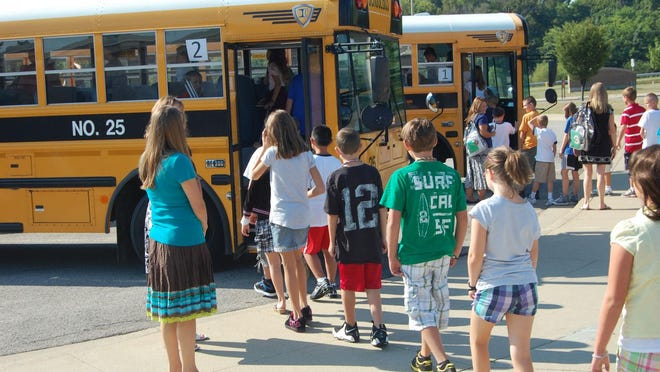 Students from Summit View Elementary in Independence are supervised as they file onto the school buses on their first day of school. Summit View received a bomb threat early in the school year, Boone County schools have faced similar threats.