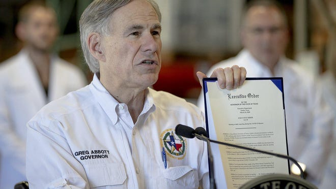 Gov. Greg Abbott, shown in late March, holds up an executive order about reporting coronavirus data.