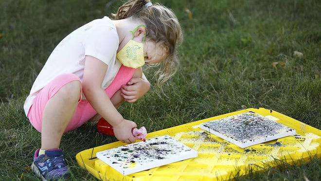 Paige Keller,5 uses a pump bottle to create a painting on the front lawn.  Kids at Camp Viva on the campus of the CATS Academy in Braintree enjoy some creative fun with other kids on Wednesday August 12, 2020 Greg Derr/The Patriot Ledger