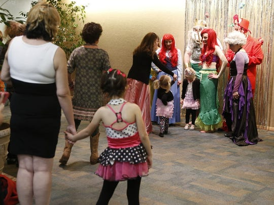 "Parents and children line up to have their photos taken with actors portraying ""The Little Mermaid"" characters during the Mom Prom on Saturday at the Farmington Civic Center."