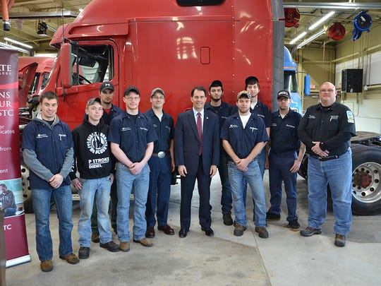 Gov. Scott Walker poses for photos with students from Mid-State Technical College's Diesel and Heavy Equipment Technician program on Monday in Wisconsin Rapids.