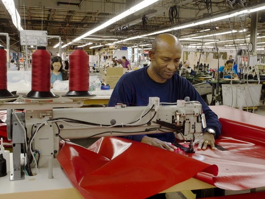Rolando Rodriguez is using a large industrial sewing