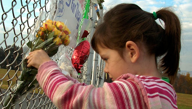 Shelby Davis, 5, whose brother Michael was a student of Assistant Principal Ken Bruce, places flowers in the fence at the entrance to Campbell County Comprehensive High School in Jacksboro, Tenn. Bruce was killed Tuesday by a student at the school. The Principal and another assistant principal were injured in the incident.