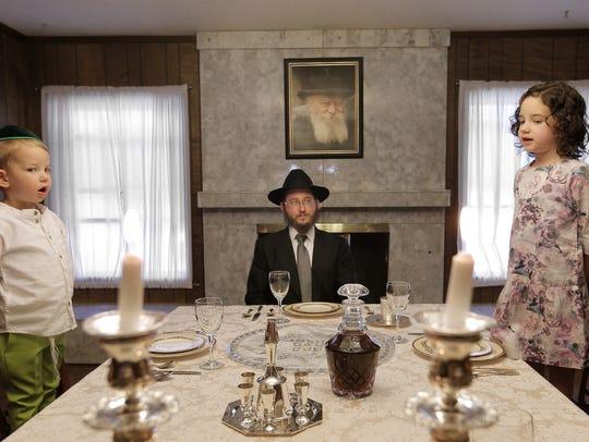 Rabbi Levi Greenberg listens as his children, Menachem,