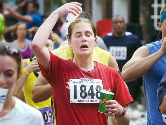 A runner cools off at a water station on Church Street