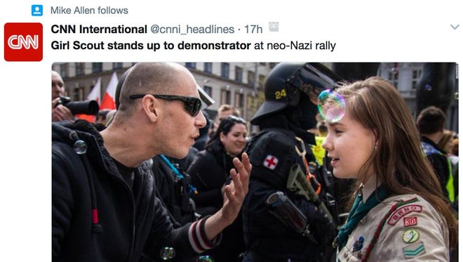 In the photo, a 16-year-old girl identified as Lucie Myslíková stares at a protestor who is gesturing angrily. Amateur photographer Vladimir Cicmanec told CNN that he took the picture after his friend pointed out the Girl Scout and the protestor.