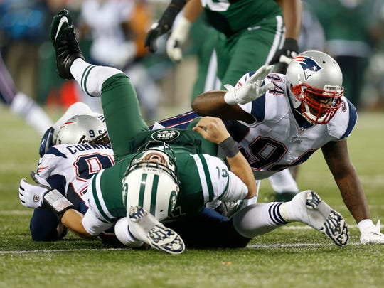 """FILE - In this Nov. 22, 2012, file photo, New York Jets quarterback Mark Sanchez is hit by New England Patriots defensive end Jermaine Cunningham (96) and Justin Francis (94) during the second half of an NFL football game in East Rutherford, N.J. For a guy who was a first-round NFL draft pick and played in a pair of AFC title games at the outset of his professional career, Sanchez knows that, fairly or not,  his name is associated with something forever known as """"The Butt Fumble.""""  (AP Photo/Julio Cortez, File)"""