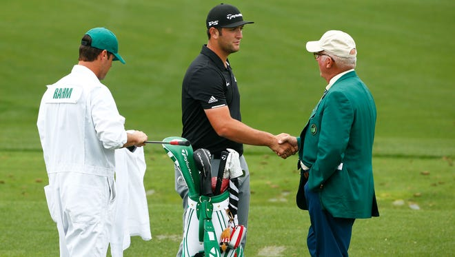 Jon Rahm is greeted by Member official Toby Wilt as the practice range is closed after the second weather warning and a tornado watch during a practice round at The Masters at Augusta National on April 3, 2017.