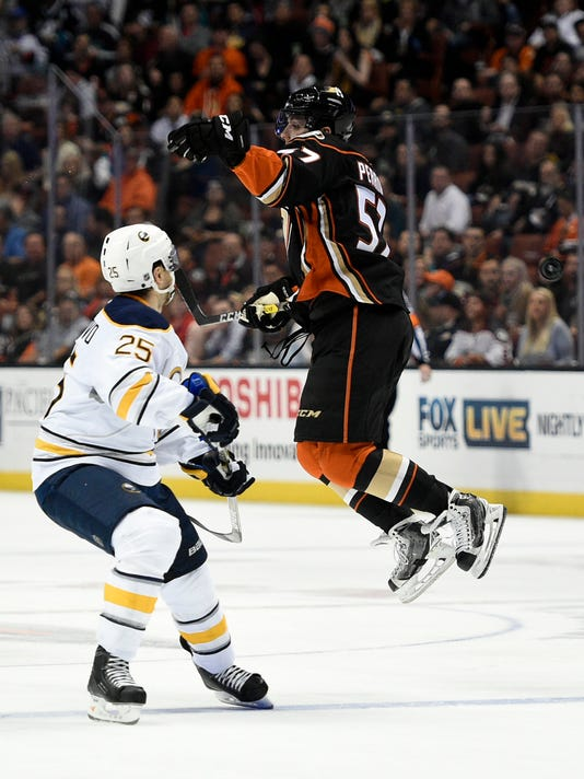 Anaheim Ducks left wing David Perron, right, jumps to block the puck as Buffalo Sabres defenseman Carlo Colaiacovo watches during the second period of an NHL hockey game in Anaheim, Calif., Wednesday, Feb. 24, 2016. (AP Photo/Kelvin Kuo)