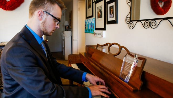 While waiting for the delivery of his new piano, East Lansing High School senior Kalil Olsen, 17, plays Aram Khachaturian's 'Toccata' Wednesday, Nov. 29, 2017, one final time on the used piano his mom paid $250 for when he was five years old.