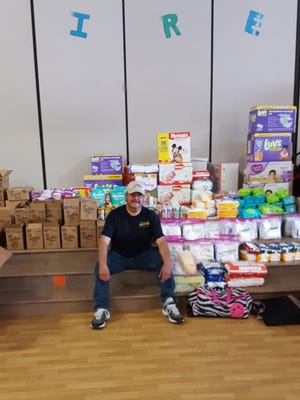 Lee Ramirez Sr., of Abilene Lodge 325 Independent Order of Odd Fellows, shows some of the supplies the group delivered to Franz Elementary School in Katy for Hurricane Harvey relief.