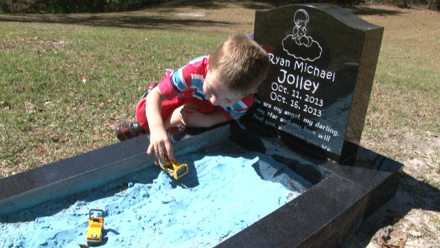 Tucker play in the sandbox that is part of his deceased, younger brother's grave.