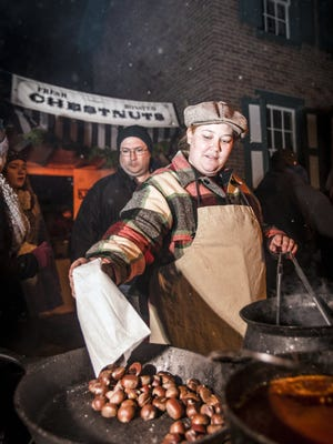 Portraying a street vendor, Amber Schwartz places a new batch of roasted chestnuts on the fire for samples during the annual Holiday Nights in Greenfield Village in 2013.