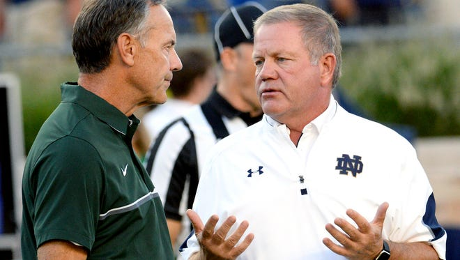 Notre Dame coach Brian Kelly, right, talks with Michigan State coach Mark Dantonio before last year's game in South Bend, Indiana. Both teams went on to miserable seasons. The misery for Kelly has continued into this season