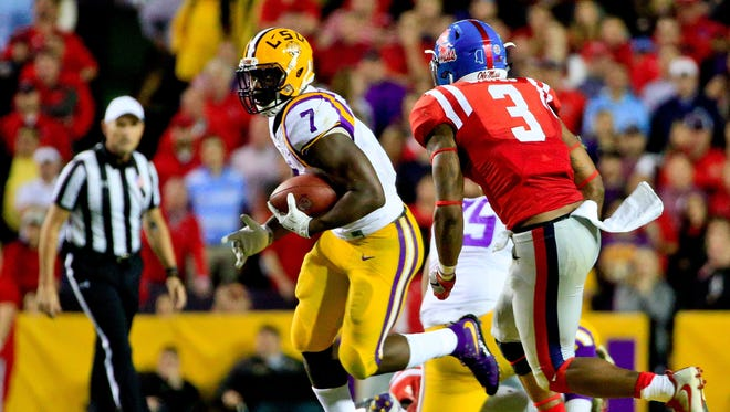 LSU Tigers running back Leonard Fournette (7) runs past Ole Miss Rebels linebacker DeMarquis Gates (3) during the second half of a game at Tiger Stadium.
