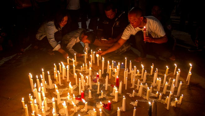 Indonesian residents light candles during a vigil for the victims of the church attacks in Surabaya.