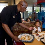 Chick-fil-A employee Tom Ponder of Atlanta gives out a sample of Chick-fil-A's new grilled chicken to 4-year-old Myla Freeman of Atlanta.