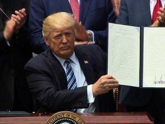 636299225399140225-Trump-signs-order.jpg