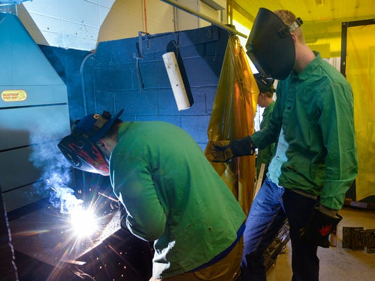 Kimball High School sophomore Jacob Lindberg, left, and Weston Hine work together to practice using an arc welder during a welding class April 21 at the school. Lindberg picked up an interest in welding from hanging out in his father's shop since the age of 10.