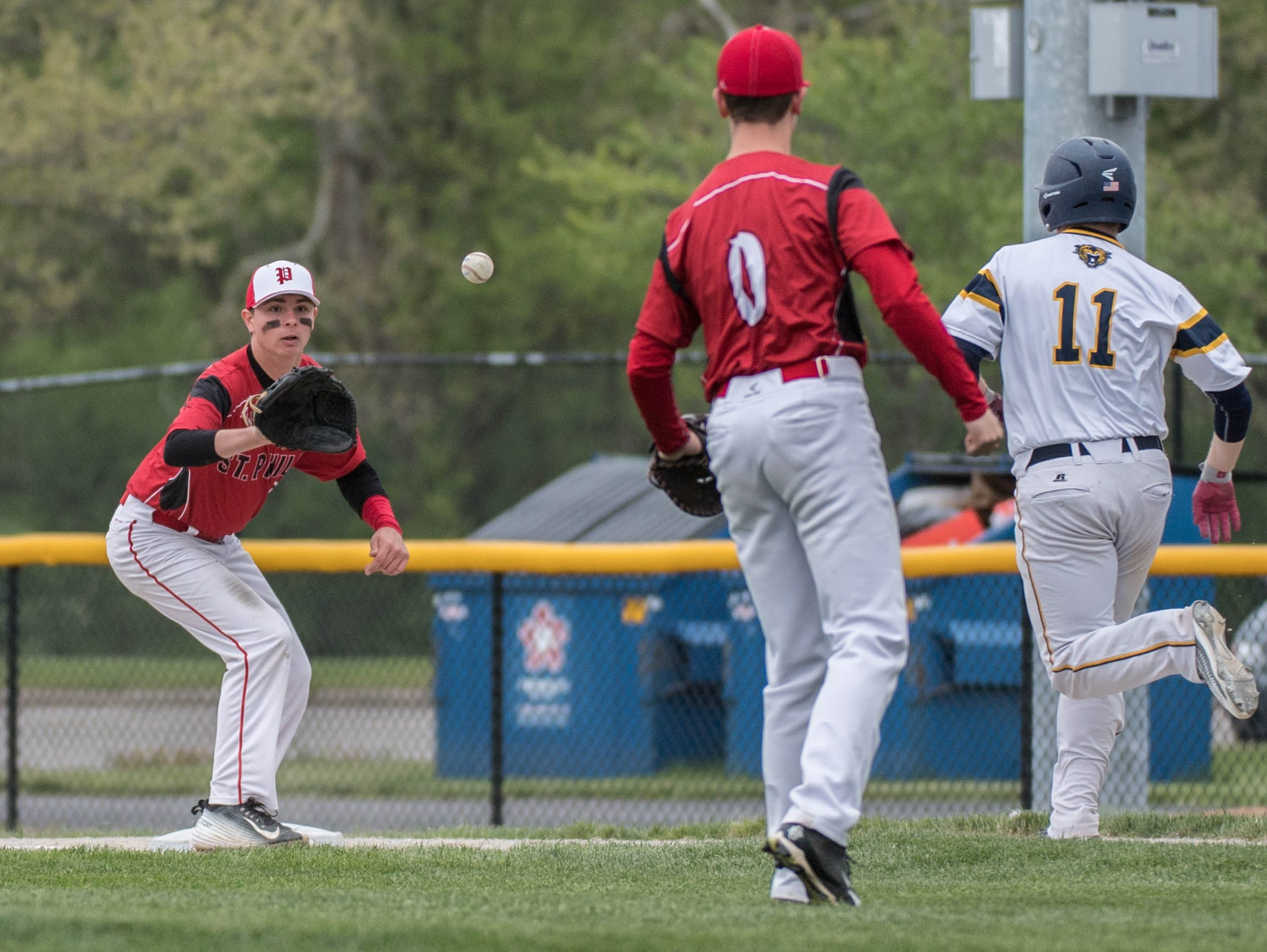 St. Philips's Drew Lantinga gets the throw from Ian Mullis (0) to get Battle Creek Central's Dallas Gillum (11) out at first during the Annual Play 4 May tribute game in honor Tim May at C.O. Brown Stadium on Monday.
