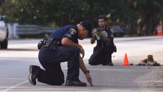 Guam Police Department crime scene investigators study the shoulder of a road in Agat where an auto-pedestrian accident occurred on April 1, 2018.