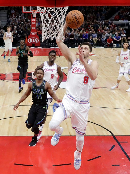 Chicago Bulls' Zach LaVine (8) scores past Dallas Mavericks' Yogi Ferrell during the first half of an NBA basketball game Friday, March 2, 2018, in Chicago. (AP Photo/Charles Rex Arbogast)