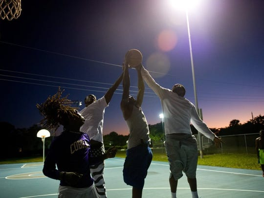 Kelvin Preston (center), gets two hands on a rebound as he is flanked by Anqueon Baker (left) and Devey Fate (right), all of Stuart, as Devineir Mitchell, of Port St. Lucie, waits at left for a loose ball during a pick-up basketball game at the courts outside the 10th Street Recreation Center on Feb. 17, 2016, in East Stuart. Ryan Carter, who was also playing basketball, said he is a lifelong resident of East Stuart, where he was born and raised for 30 years. 'I've been coming out here since I was knee high,' he said. 'A lot of times, most of the time, if there is any conflicts or anything, it's really from outside,' Carter added.